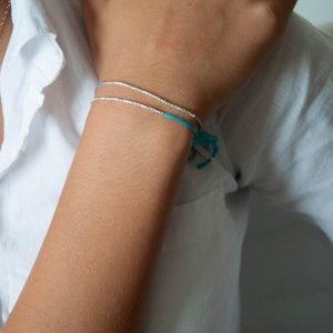 Delicate silver bracelet on Turquoise silk